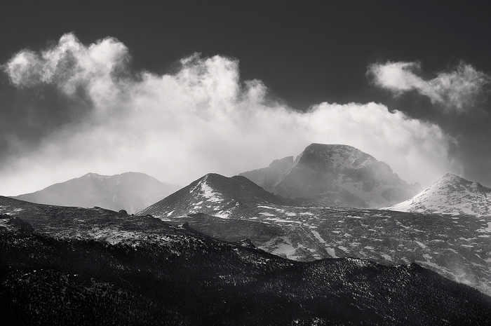 Wind-blown snow and clouds circle the Longs Peak summit