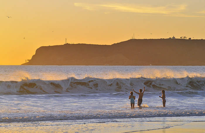 Children enjoying incoming waves on Coronado Island.