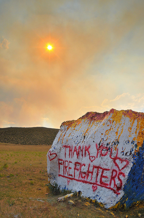 A tribute to firefighters is painted on a boulder near U.S. Highway 287 north of Fort Collins.
