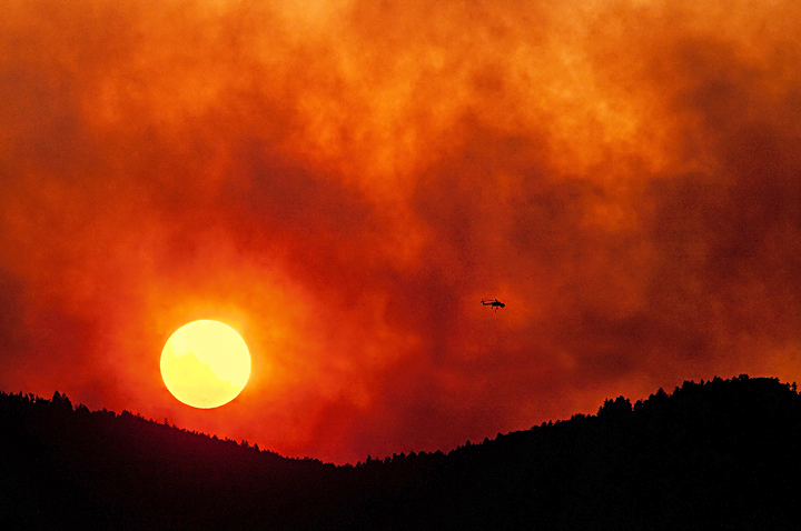 A sky crane looks like a minuscule ant working against a massive backdrop of wildfire smoke.