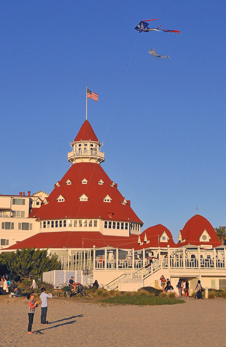 Children flying kites in front of the historic Hotel del Coronado.