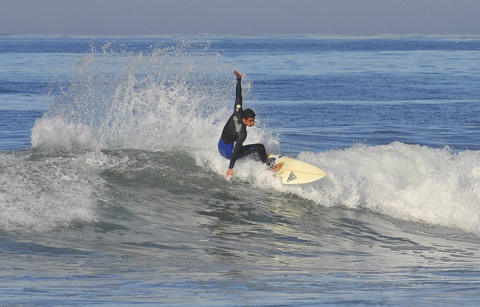 A surfer catches a wave at Pacific Beach.